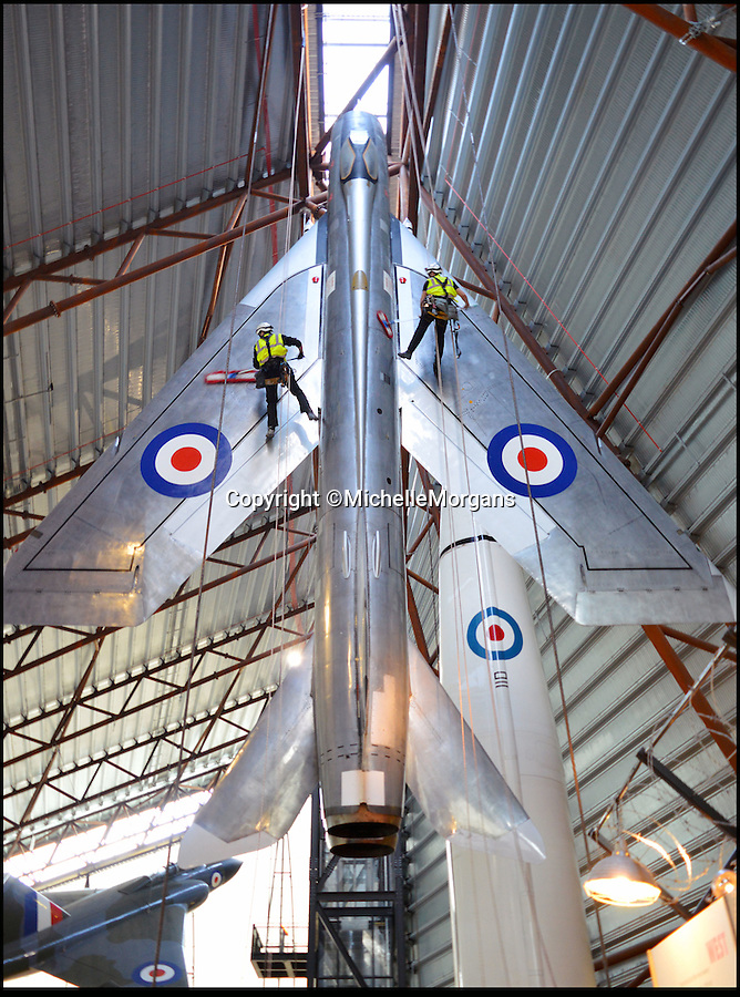 BNPS.co.uk (01202 558833)<br /> Pic: MichelleMorgans/BNPS<br /> <br /> On a wing and a prayer… the acrobatic dusting team gets to work sprucing up the spectacular hanging aircraft at RAF Cosford museum.<br /> <br /> A specialist team of daredevil cleaners wearing hard hats abseil down the magnificent aircraft to give them their annual clean so that they look their best for visitors to the museum this coming year.<br /> <br /> The job of cleaning the aircraft has taken the team at Staffordshire firm Total Access, which also cleans bridges, football stadiums and high rise buildings, all week.<br /> <br /> They climbed up the side of the 60ft hanger then abseiled down the aircraft wielding mops.<br /> <br /> The largest suspended aircraft they cleaned was the Vulcan, which is 102ft long and has a wingspan of 99ft. They also tackled the vertically hanging Lightning.