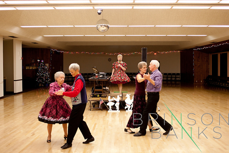 Anne Brown Rigg calls during a round dance as couples pass by during a night of round and square dancing in a social hall in Sun City, Arizona December 8, 2009. Because there are less men available, some women have to dance together.
