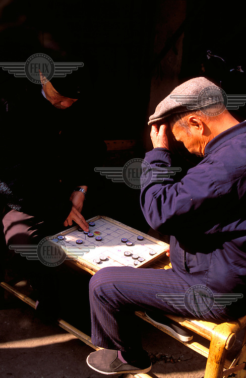 © Chris Stowers / Panos Pictures..Fuzhou, CHINA..Old men playing a board game in the back streets.