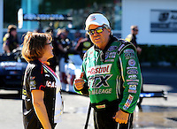 Mar 14, 2014; Gainesville, FL, USA; NHRA funny car driver John Force (right) talks with sponsor Charlotte Lucas during qualifying for the Gatornationals at Gainesville Raceway Mandatory Credit: Mark J. Rebilas-USA TODAY Sports