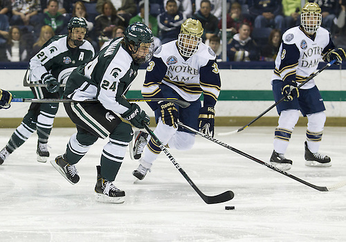 December 07, 2012:  Michigan State forward Justin Hoomaian (#24) skates with the puck as Notre Dame defenseman Shayne Taker (#3) defends during NCAA Hockey game action between the Notre Dame Fighting Irish and the Michigan State Spartans at Compton Family Ice Arena in South Bend, Indiana.  Notre Dame defeated Michigan State 3-2.