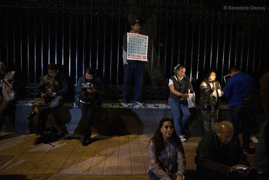 Demonstrators, along with the Parents and relatives of the 43 missing students of the Ayotzinapa Teacher Training College Raul Isidro Burgos, hold candles during a New Year's Eve protest near Los Pinos presidential residence in Mexico City, Mexico on December 31, 2014. The relatives of the 43 missing students do not believe the official line that the young men are all dead. The 43 students went missing on Sept. 26 after confrontations in which police gunfire killed six people and wounded at least 25 in Iguala, in Guerrero state. Alexander Mora Venancio, one of the 43 Ayotzinapa's missing students, has been identified and confirmed dead by authorities. Many are demanding justice and that the search for the 42 missing students continue until there is concrete evidence to the contrary. Mexico – officially - lists more than 20 thousand people as having gone missing since the start of the country's drug war in 2006, and the search for the missing students has turned up other, unrelated mass graves. (Photo by Bénédicte Desrus)