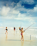 USA, Florida, young woman fishing at New Smyrna Beach