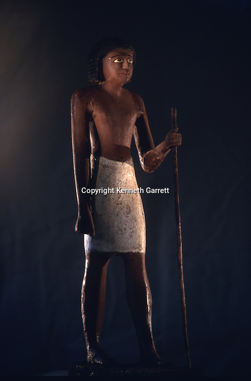 Standing wooden statue of an official holding a staff, Old Kingdom