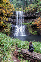 A woman sits and watches the Lower South Falls at Silver Falls State Park in Oregon.