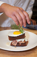 Chef preparing the Croque Madame, brioche with Ham, truffled béchamel, gruyere these and sunny side up egg at The Barberry in McMinnville, Oregon
