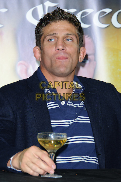 Alex Reid.Alex Reid makes announcement about forthcoming Cage Fight, London, England..July 20th, 2011.half length blue  white striped stripes top jacket black champagne drink glass beverage hand funny.CAP/CJ.©Chris Joseph/Capital Pictures.