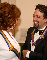 Reba McEntire, left, and Lin-Manuel Miranda, right, two of the recipients of the 41st Annual Kennedy Center Honors converse prior to posing for a group photo following a dinner hosted by United States Deputy Secretary of State John J. Sullivan in their honor at the US Department of State in Washington, D.C. on Saturday, December 1, 2018.  The 2018 honorees are: singer and actress Cher; composer and pianist Philip Glass; Country music entertainer Reba McEntire; and jazz saxophonist and composer Wayne Shorter. This year, the co-creators of Hamilton,? writer and actor Lin-Manuel Miranda; director Thomas Kail; choreographer Andy Blankenbuehler; and music director Alex Lacamoire will receive a unique Kennedy Center Honors as trailblazing creators of a transformative work that defies category.<br /> CAP/MPI/RS<br /> &copy;RS/MPI/Capital Pictures