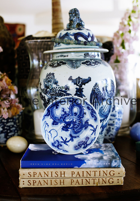 A still life of blue and white Chinese ceramics is displayed on the central table in the living room