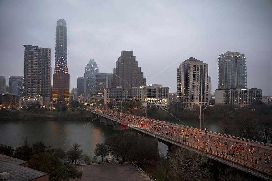 Fog covers the Austin skyline on a moody day in February as thousands of Austin Marathon runners take over Congress Avenue Bridge after the start of the race in downtown Austin, Texas.<br />