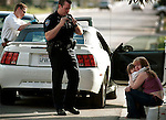STOLEN CAR--Redlands Police officer Dan Elton, center, talks on his radio while CPL Ken Wright, left, searches a vehicle that was caught after a chase on Church Avenue near Harlan Lane in Highland, Monday, December 3, 2001. The automobile was followed involving a bad check scheme and apprehended when it was discovered to be stolen. The 16-year-old woman on the curb and her daughter were detained for questioning and released.