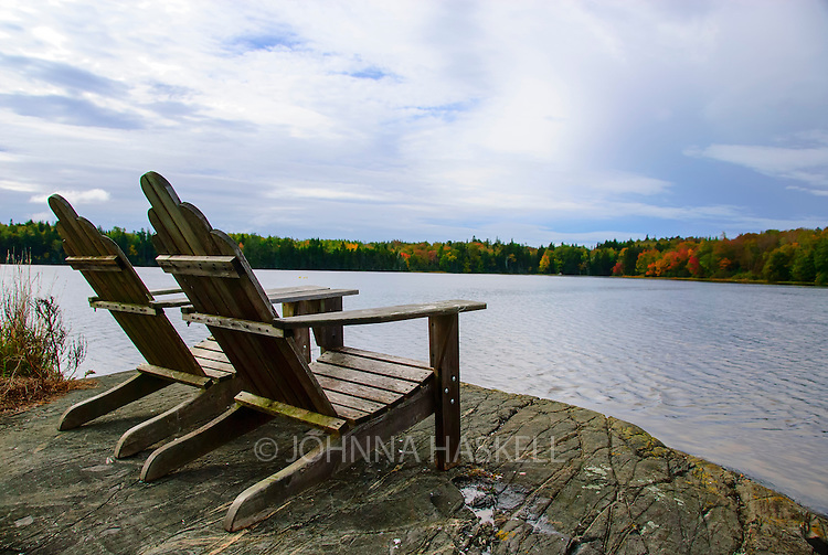 Adirondack chairs overlook the bay during high tide on Deer Isle, Maine in fall.