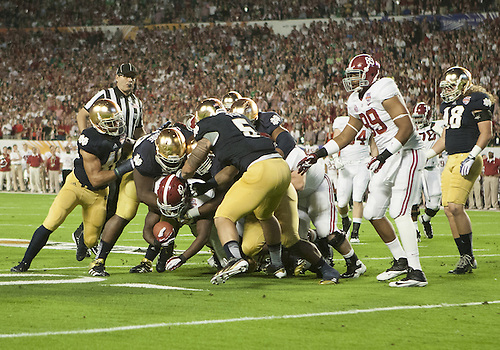 January 7, 2013:  Alabama running back Eddie Lacy (42) is tackled by a host of Notre Dame defenders during the Discover BCS National Championship between the Alabama Crimson Tide and the Notre Dame Fighting Irish at Sun Life Stadium in Miami Gardens, Florida.  Alabama defeated Notre Dame 42-14.