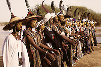 Akadaney, Niger, Africa - Fulani Wodaabe Dancers at Geerewol, often referred to by westerners as the male beauty contest, in which the whiteness of the eyes and the teeth is an important factor in appealing to the female spectators.  Many dancers wear large red and green leather wallets on a cord around their necks.  Others wear red leather amulets, usually with Koranic verses inside for protection or good luck.  On some costumes cowrie shells form a fringe on the bottom, though this site is a thousand miles from the nearest sea coast.