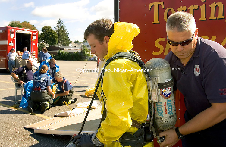 TORRINGTON, CT-10 SEPTEMBER 2006-091006JS03-Torrington firefighter Jim Cosgrove, right, helps prepare Torringford Volunteer firefighter Brian Lebatique for his assignment during a mock toxic chemical spill Sunday at the Timken Industrial plant in Torrington. Three simultaneous mock haz-mat incidents took place in Danbury, Waterbury and Torrington to test the emergency response of the newly formed Northwest Regional Hazardous Materials Team. The teams were to test communications between local, regional and state agencies and the preparedness of emergency workers and first responders.  -Jim Shannon Republican-American