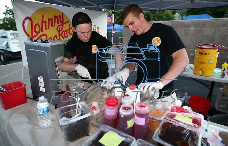 Clint Page, left, and Jake Myers work in the Johnny Rockets booth atd the 20th annual Taste of Downtown event in Carson City, Nev., on Saturday, June 15, 2013. The event features 44 local restaurants in a fundraiser for the Advocates to End Domestic Violence.<br /> Photo by Cathleen Allison