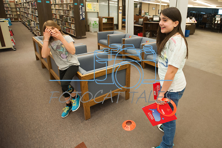 Katie Tubiello, right, and Sandra Tubiello look for course ideas during the Mini Golf Night at the Carson City Library on Friday, May 9, 2014. Kids and parents built a custom mini golf course throughout the library using anything at their disposal and engineering ideas to make a difficult course. Everything from tables to shelves were used to create creative courses.<br />