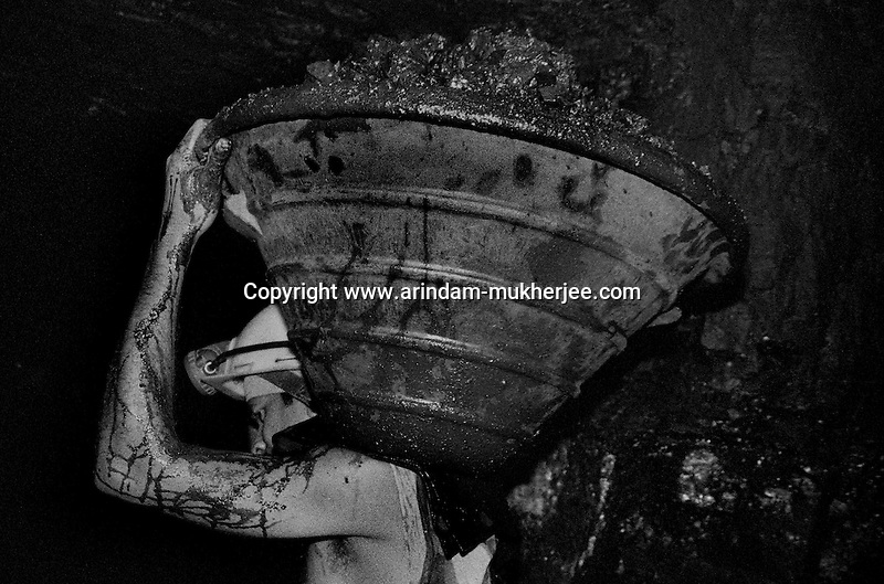 A miner carrying a  bucket of coal on his shoulder. Ranigunj, West Bengal, India. Arindam Mukherjee