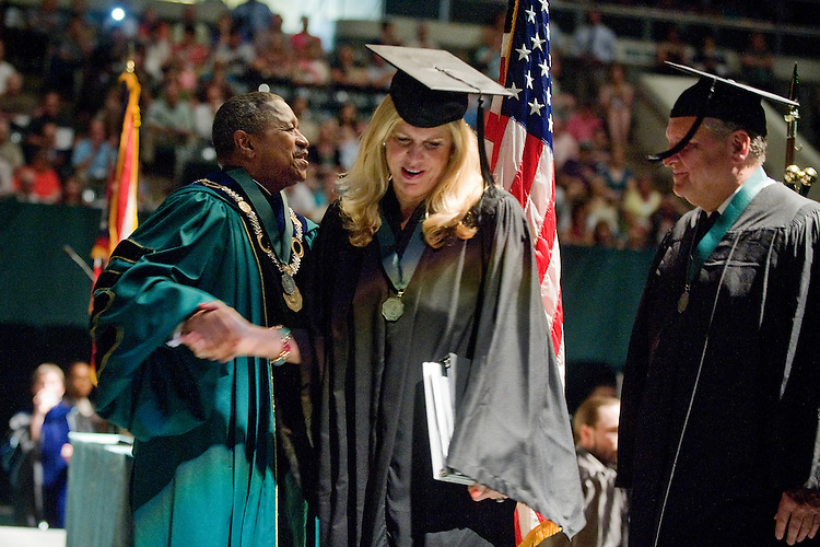Ohio University's 2010 undergraduate commencement speaker, Melanie Sabelhaus, center, shakes hands with President Roderick McDavis Saturday, June 12, 2010 after walking with her class, the class of 1970 at Ohio University's Convocation Center. She is followed on-stage by her husband, Bob.