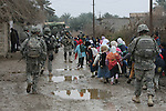 "A group of schoolchildren in the village of Himbiss, Iraq walk alongside a patrol of U.S. soldiers from 3rd Squadron, 2nd Stryker Cavalry Regiment. Said one soldier, ""We just came out onto the street, and they started following us.""  The soldiers are part of Operation Iron Harvest, which is meant to kill or capture al Qaida fighters who fled into rural areas of Diyala province after the U.S. troop surge in Baghdad and Baqubah last year. Jan. 23, 2008. DREW BROWN/STARS AND STRIPES"