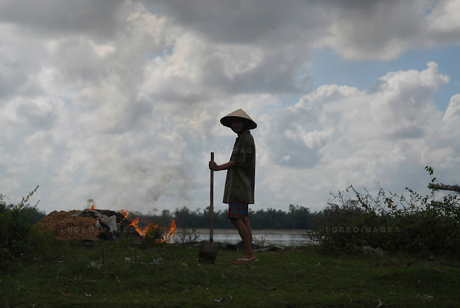 A Vietnamese worker burns trash on the side of the road outside of Hoi An, Vietnam.