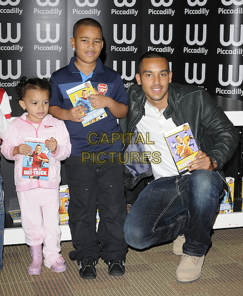 THEO WALCOTT & fans .Footballer Theo Walcott attending his booksigning session at Waterstone's Piccadilly, London, England, UK, November 4th 2010..book signing  full length black jacket leather jeans white t-shirt children kids Arsenal top shirt kneeling down grey gray .CAP/CAN.©Can Nguyen/Capital Pictures.