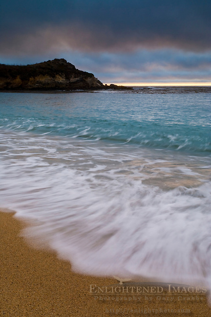 Waves breaking on sand beach at sunset, Carmel River State Beach, California