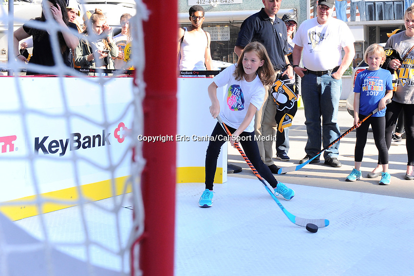 May 29, 2017: A young fan tries her hand at scoring a goal before game one of the National Hockey League Stanley Cup Finals between the Nashville Predators  and the Pittsburgh Penguins, held at PPG Paints Arena, in Pittsburgh, PA. Pittsburgh defeats Nashville 5-3 in regulation time.  Eric Canha/CSM