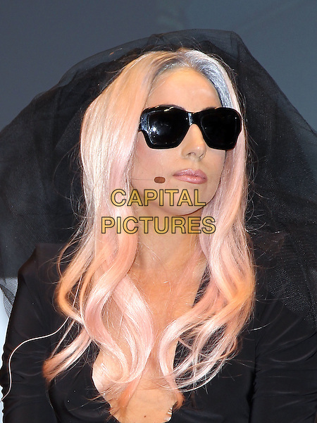 LADY GAGA (Stefani Joanne Angelina Germanotta).Lady Gaga and Polaroid unveil new products at 2011 CES at the Las Vegas Convention Center,  Las Vegas, Nevada, USA, 6th January 2011..portrait headshot  black veil sunglasses pink dyed hair wig corset bustier top  low cut microphone .CAP/ADM/MJT.© MJT/AdMedia/Capital Pictures.