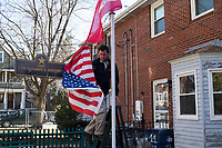 "Carlos Arredondo, 57, hangs a Marine flag and American flag, in his front yard where there's a memorial to his two sons Brian and Alex Arredondo, at his home in Roslindale, Boston, Massachusetts, USA, on Sat., March 31, 2018. Arredondo is well known as the ""man in the cowboy hat"" who helped out in the aftermath of the Boston Marathon Bombing in 2013. His son, Marine Lance Corporal Alexander Scott Arredondo, was killed while serving in the military in Iraq in 2004. Brian died by suicide in 2011 after a battle with depression after his brother's death."