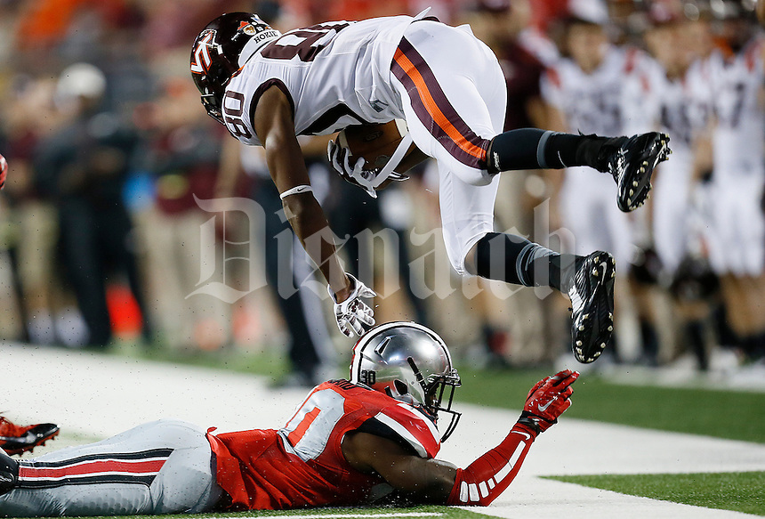 Ohio State Buckeyes linebacker Devan Bogard (30) flips Virginia Tech Hokies wide receiver Demitri Knowles (80) in the third quarter of the college football game between the Ohio State Buckeyes and the Virginia Tech Hokies at Ohio Stadium in Columbus, Saturday afternoon, September 6, 2014. The Virginia Tech Hokies defeated the Ohio State Buckeyes 35 - 21. (The Columbus Dispatch / Eamon Queeney)