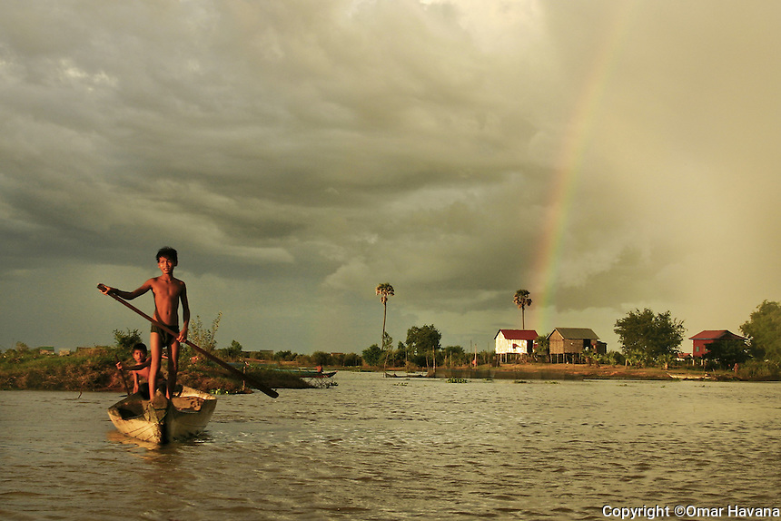 SIEM REAP, CAMBODIA. Residents of the community use boats to move over the land where they normally live before the water of the Tonle Sap Lake rise with the arrival of the monsoon rain. The entire village is under water after the arrival of the wet season to Cambodia, reason why the families they are forced to move to a new location until the monsoon will end. Almost 200 people live in a community on the shore of the Tonle Sap Lake, just few kilometers away from the city of Siem Reap, home to the world famous temples of Angkor. Photo: ©Omar Havana