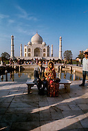 Agra, India, January 1975: A newly wedded couple in front of the Taj Mahal located in Agra, India. Taj Mahal is a white marble mausoleum built by Mughal emperor Shah Jahan in memory of his third wife, Mumtaz Mahal. Taj Mahal is the finest example of Mughal architecture, a style that combines elements from Persian, Turkish and Indian architectural styles and also considered as one of the seven wonders of the world. In 1983, the Taj Mahal became a UNESCO World Heritage Site.