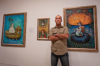 Cuban Artist Eduardo Miguel Abela Torras poses in front of his works at The von Liebig Art Center, after the ribbon cutting ceremony to launch the 'Cuba on My Mind' exhibit, March 10, 2011. Photo by Debi Pittman Wilkey
