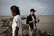 27 year old Maskuri (in cap) and his friend, Daryono (23) seen catching fish on the shores of Java sea in Tegal of Central Java region in Indonesia. Photo: Sanjit Das/Panos