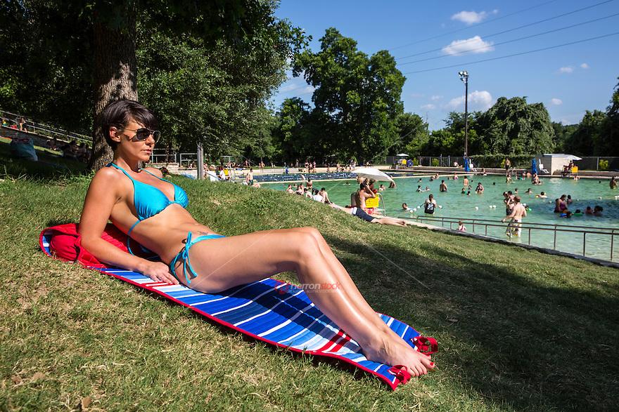 Attractive model in bikini at Deep Eddy Pool, sunbathing on sunny day in Austin, Texas.