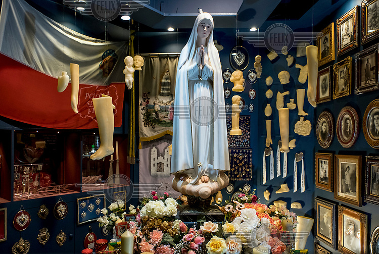 A display in the museum at the Sanctuary of Fatima of Our Lady of Fatima surrounded by ex votos, photographs, flowers and medaillons.