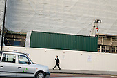 A man speaking on a mobile phone walks past a construction site in the City of London.