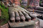 _DSC1341, Vacheron, China, 02/2016, CHINA-10360. A monk walks among the feet of a large Buddha statue.<br /> CHECK IMAGE USAGE<br /> <br /> Leshan Giant Buddha. China, 2016.<br /> <br /> FINAL_Vacheron<br /> <br /> Retouched_Sonny Fabbri 03/22/2016