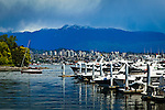 Boats at Coal Harbour, Vancouver, B.C, Canada in early summer. Buildings and a mountain are in the background. Dramatic clouds look menacing on the horizon. A small red boat cruises through the marina.