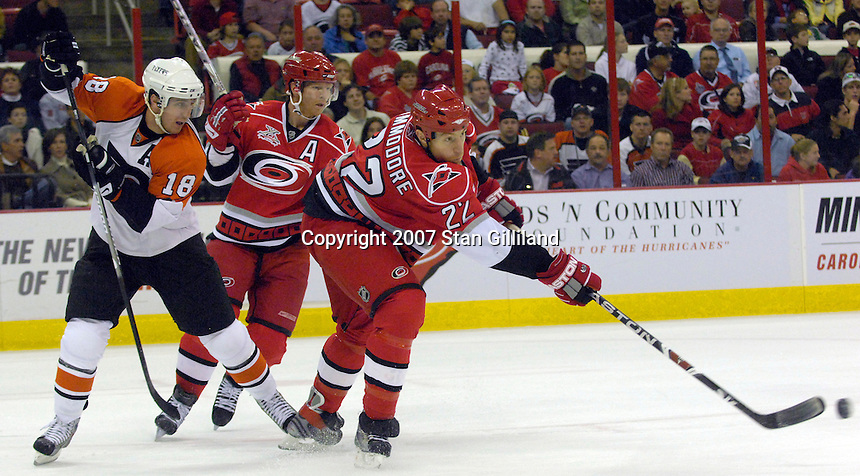 The Philadelphia Flyers' Mike Richards (18) defends as the Carolina Hurricanes' Mike Commodore (22) passes and teammate Glen Wesley (2) follows during their game Wednesday, Nov. 21, 2007 in Raleigh, NC. The Flyers won 6-3.