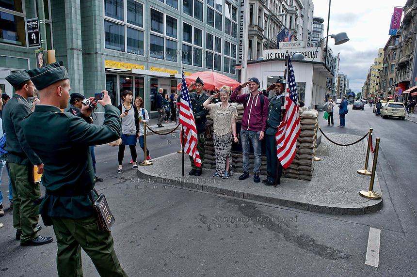 Berlino 15 Settembre 2013<br /> Attori che interpretano  militari dell'esercito degli Stati Uniti d'America  in posa per foto ricordo con i turisti al Checkpoint Charlie.<br /> Actors playing a United States Army military posing for souvenir photos with tourists at former Checkpoint Charlie