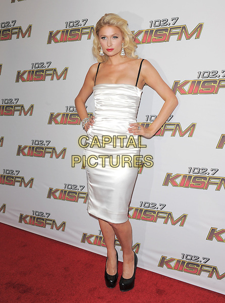 PARIS HILTON.Pressroom at the KIIS FM Wango Tango 2011 held at The Staples Center in Los Angeles, California, USA. .May 14th, 2011.full length white dress hands on hips black shoes silk satin straps .CAP/RKE/DVS.©DVS/RockinExposures/Capital Pictures.