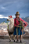A Peruvian woman dressed in traditional clothing stands with her llama in Cuzco, Peru.