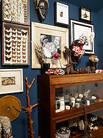 Against the dark blue walls of a windowless basement area leading off the kitchen/dining area a collection of tribal art and finds of nature is displayed