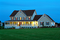 The front exterior of an executive style country home with the lights on at dusk.