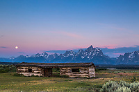 Sunrise and a setting moon over the Grand Tetons, at the historic Cunningham Pioneer Cabin in Grand Teton National Park<br />