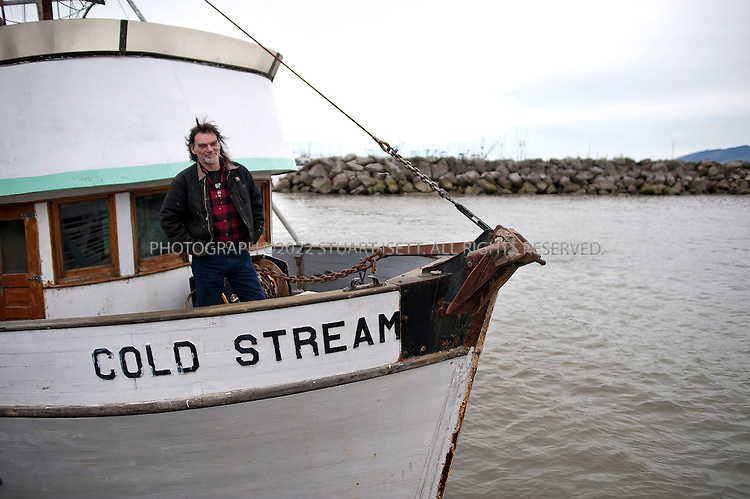 2/28/2009--Astoria, OR, USA..Dave Densmore greets visitors on his boat, the Cold Stream, during an open house during The Fisher Poets Gathering. The festival is an annual event held on the last weekend of February in Astoria, Oregon, where men and women somehow tied to the fishing industry get together to share their poems, tales, and songs. Begun in 1998 the festival has greatly expanded and now attracts around 60-70 artists and hundreds of audience member..©2009 Stuart Isett. All rights reserved.
