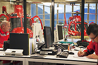 "Switzerland. Canton Ticino. Locarno Airport LSZL. The Rega base's official name is Locarno LSMO AFB (Rega 6). The pilot Corrado Sasselli (L) and the doctor Michele Musiari (R) sit at their desks and fill in administrative documents upon return from a rescue operation. Behind a glass window, two Rega Agusta AW109 SP Grand ""Da Vinci"" helicopters. On the right, the chopper used daily for rescue missions. On the left, a second helicopter used during a two weeks program provided as permanent staff training on a turnover basis for Rega crews from allover Switzerland.  All Rega helicopters carry a crew of three: a pilot, an emergency physician, and a paramedic who is also trained to assist the pilot for radio communication, navigation, terrain/object avoidance, and winch operations. The name Rega was created by combining letters from the name ""Swiss Air Rescue Guard"" as it was written in German (Schweizerische Rettungsflugwacht), French (Garde Aérienne Suisse de Sauvetage), and Italian (Guardia Aerea Svizzera di Soccorso). Rega is a private, non-profit air rescue service that provides emergency medical assistance in Switzerland. Rega mainly assists with mountain rescues, though it will also operate in other terrains when needed, most notably during life-threatening emergencies. As a non-profit foundation, Rega does not receive financial assistance from any government. The AgustaWestland AW109 is a lightweight, twin-engine, helicopter built by the Italian manufacturer Leonardo S.p.A. (formerly AgustaWestland, Leonardo-Finmeccanica and Finmeccanica). Leonardo S.p.A is an Italian global high-tech company and one of the key players in aerospace. In close collaboration with the manufacturer, the Da Vinci has been specially designed to cater for Rega's particular requirements as regards carrying out operations in the mountains. It optimally fulfills the high demands made of it in terms of flying characteristics, emergency medical equipment and maintenance. Safety, performance"