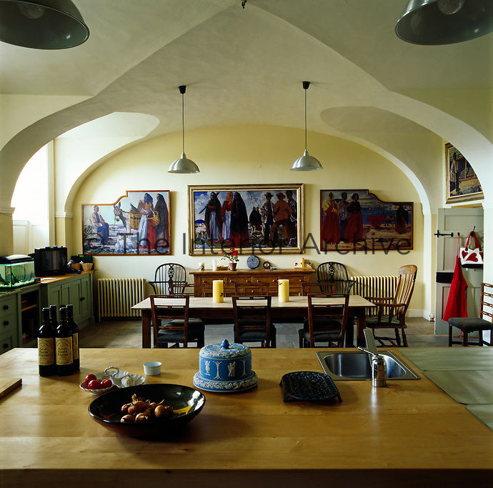 The kitchen/dining room has a triptych of paintings on the far wall and an impressive vaulted ceiling